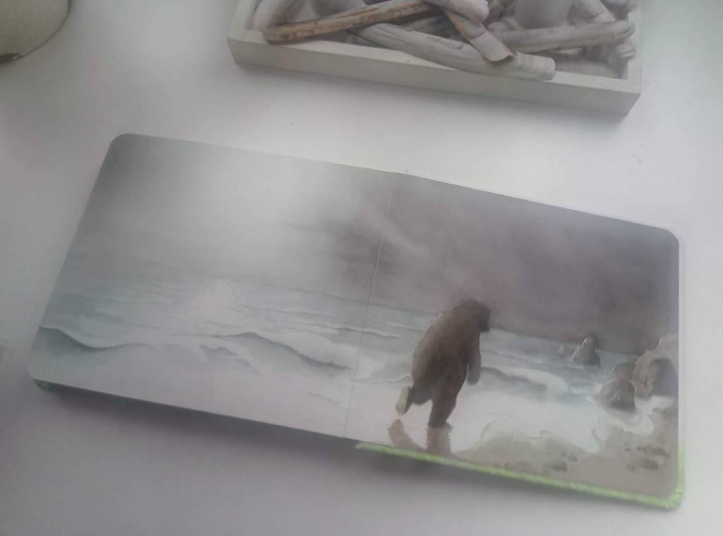 """Последната страница на книгата """"Отиваме на лов за мечки"""": мечката върви на два крака по плажа и се отдалечава навъсено."""
