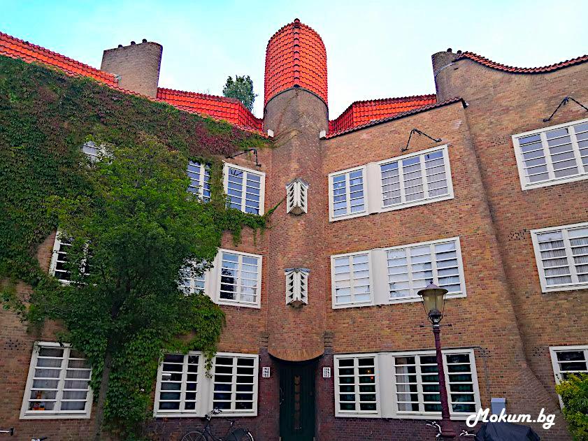Декорация под формата на овални форми, вълнисти извивки и облицовка на част от стените с керемиди са типични за архитектурния стил Amsterdamse School. Снимка на част от забележителния жилищен проект De Dageraad в de Pijp.